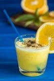 Wyśmienicie sok pomarańczowy w szkle i pomarańcze obok go na błękitnym tle Zdjęcia Stock