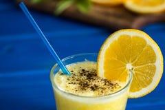 Wyśmienicie sok pomarańczowy w szkle i pomarańcze obok go na błękitnym tle Obrazy Stock