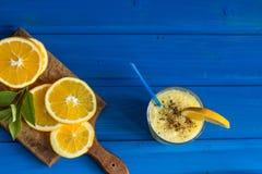 Wyśmienicie sok pomarańczowy w szkle i pomarańcze obok go na błękitnym tle Zdjęcie Stock