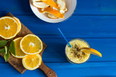 Wyśmienicie sok pomarańczowy w szkle i pomarańcze obok go na błękitnym tle Fotografia Royalty Free