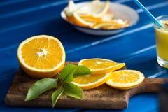 Wyśmienicie sok pomarańczowy w szkle i pomarańcze obok go na błękitnym tle Zdjęcie Royalty Free