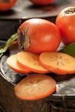 Wyśmienicie surowa dojrzała persimmon owoc na ciemnym ośniedziałym metalu backgroun zdjęcia royalty free