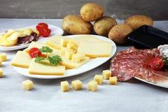 Wyśmienicie tradycyjny szwajcar topił raclette ser na diced czyraku obraz stock