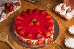 Wyśmienicie truskawka tort na drewnianym stole z składnikami Obrazy Royalty Free