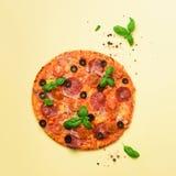 Wyśmienicie włoska pizza, basilów liście, sól, pieprz na żółtym tle z copyspace Kwadratowa uprawa Odgórny widok sztandar obraz royalty free