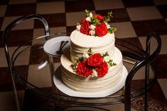 Wyśmienicie wielopoziomowy ślubny tort na szklanej tacy z talerzami i łyżkami obrazy stock