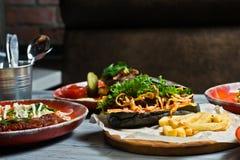 Wyśmienity mięsnych posiłków asortyment Boczny widok na restauracja stole z menu smakowity hot dog, grill wieprzowiny ziobro, ste obrazy stock