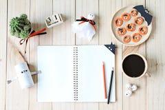 Wyśmiewa up otwarty notatnik, papierowi rzemiosła, sześcianu kalendarz, piec na grillu marchewki z straszną twarzą i filiżanka, Zdjęcia Stock