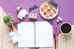Wyśmiewa up otwarty notatnik, papierowi rzemiosła, sześcianu kalendarz, piec na grillu marchewki z straszną twarzą i filiżanka, Zdjęcia Royalty Free