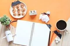 Wyśmiewa up otwarty notatnik, papierowi rzemiosła, sześcianu kalendarz, piec na grillu marchewki z straszną twarzą i filiżanka, Obrazy Royalty Free