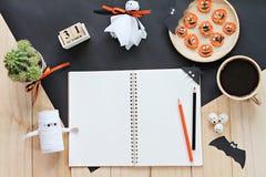 Wyśmiewa up otwarty notatnik, papierowi rzemiosła, sześcianu kalendarz, piec na grillu marchewki z straszną twarzą i filiżanka, Zdjęcie Stock
