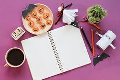 Wyśmiewa up otwarty notatnik, papierowi rzemiosła, sześcianu kalendarz, piec na grillu marchewki z straszną twarzą i filiżanka, Fotografia Stock