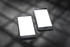 Wyśmiewa w górę czarnych smartphones na szarym tle z cieniem kratownica obraz royalty free