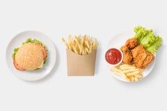 Wyśmiewa w górę hamburgeru, francuzów dłoniaków i pieczonego kurczaka ustawiającego odizolowywającym, obrazy royalty free