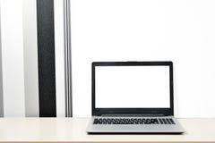 Wyśmiewa w górę laptopu, notatnik na biurku na minimalistic czarny i biały tło ścianie zdjęcia royalty free