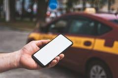 Wyśmiewa w górę smartphone w ręce, na tle taxi samochód obrazy royalty free