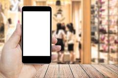 Wyśmiewa w górę wizerunku trzyma czarnego telefon komórkowego z pustym bielu ekranem ręka Zdjęcie Royalty Free