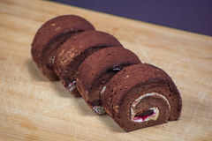 Wyśmienicie czekoladowa rolka w talerzu na drewnianej deski tle Fotografia Stock