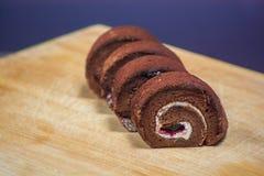 Wyśmienicie czekoladowa rolka w talerzu na drewnianej deski tle Zdjęcie Stock