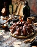 Wy?mienicie domowej roboty czekoladowy bundt tort na drewnianych talerzy stojakach na wie?niaka stole zdjęcie royalty free