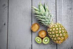 Wyśmienicie kiwi i ananasa owoc na popielatym drewnianym tle Zdjęcia Royalty Free