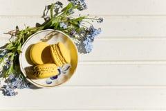 Wyśmienicie kolorowi macaroons na modnego rocznika drewnianym stole z niezapominajka kwiatami i confetti, mieszkanie nieatutowy s Obraz Stock