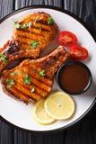 Wy?mienicie piec na grillu wieprzowina stek w korzennym tamarynda kumberlandzie z cytryn? i ?wie?ym pomidoru zbli?eniem na talerz obraz royalty free
