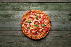 Wyśmienicie pizza z serem i pomidorami na nieociosanym drewno stole Fotografia Stock