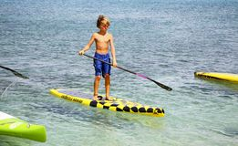 Wyatt Bracy on stand up paddle board. Wyatt Bracy, aged 9, of St. Croix competed with the pros in the 10K race. The Coconut Cup Stand Up Paddle Boarding SUP Stock Photography