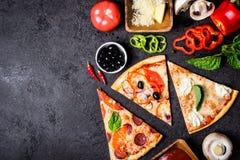 Wybór Asortowana kawałek pizza na czarnych składnikach i tle Pepperoni, jarosza i owoce morza pizza, obraz stock