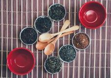 Wybór herbaty, czerwone filiżanki i drewniane łyżki na bambusie, Matujemy Obraz Royalty Free
