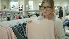 Wybór kobiet szaty w sklepie, dziewczyna shopaholic robi zakupom kobiety odzieżowa sprzedaż, rozmaitość rzeczy wieszać zbiory