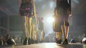 Wybieg modeluje w eleganckiej todze i moda sandały pokazuje nową kolekcję odziewają na scenie w oświetleniowym reflektorze w zdjęcie wideo