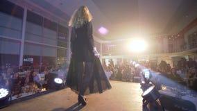 Wybieg wzorcowa dziewczyna w wieczór czerni długą suknię w szpilkach beszcześci na podium przy mody wydarzeniem w reflektor zdjęcie wideo
