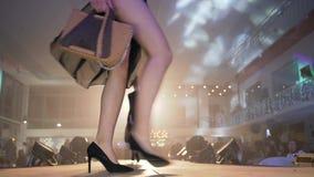 Wybieg wzorcowa kobieta w szpilki buty w czarną modną suknię chodzi na podium przy jaskrawym światło reflektorów przed zbiory wideo