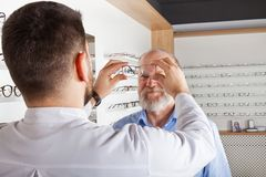 Wybierać eyeglasses w okulistycznym sklepie fotografia stock