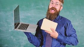Wybiera prawą nauczanie metodę Nauczyciel wybiera nowożytnego nauczania podejście Nauczyciela modnisia brodaci chwyty książka i l zdjęcia stock