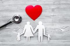 Wybiera ubezpieczenie zdrowotne Stetoskop, papierowy serce i sylwetka rodzina na popielatym drewnianym tło odgórnego widoku copys obraz stock