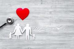 Wybiera ubezpieczenie zdrowotne Stetoskop, papierowy serce i sylwetka rodzina na popielatym drewnianym tło odgórnego widoku copys Zdjęcie Stock