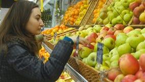 Wybierający jabłko i kupujący przy sklepem Obrazy Royalty Free