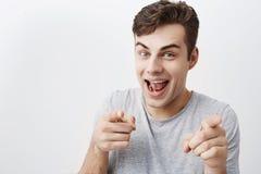 Wybieram ciebie! Pozytywna emocjonalna samiec z ciemnego włosy spojrzeniami przy kamerą z radością i punktami z forefingers przy  fotografia stock