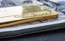 Wybijający monety złocisty bar waży 50 gramów 999 9, finezja przeciw tłu dolarowi rachunki fotografia royalty free