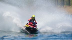 Jet Ski competitor cornering at speed creating at lot of spray. WYBOSTON, BEDFORDSHIRE, ENGLAND -  APRIL 09, 2017: Jet Ski competitor cornering at speed Royalty Free Stock Image