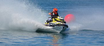 Jet Ski competitor cornering at speed creating at lot of spray. WYBOSTON, BEDFORDSHIRE, ENGLAND -  APRIL 09, 2017: Jet Ski competitor cornering at speed Royalty Free Stock Photos