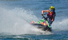 Jet Ski cornering at speed creating at lot of spray. WYBOSTON, BEDFORDSHIRE, ENGLAND -  APRIL 09, 2017: Jet Ski cornering at speed creating at lot of spray Royalty Free Stock Images
