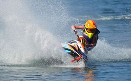 Jet Ski cornering at speed creating at lot of spray. WYBOSTON, BEDFORDSHIRE, ENGLAND -  APRIL 09, 2017: Jet Ski cornering at speed creating at lot of spray Royalty Free Stock Image