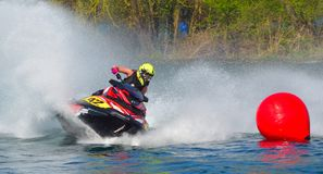 Jet Ski racer cornering around buoy at speed creating at lot of spray. Stock Photography
