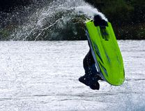 Freestyle Jet Skier performing Back Flip  creating at lot of spray. Stock Image
