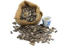 Wybrana ostrość słonecznikowi ziarna na podłoga, filiżanka gorąca herbata a Obraz Royalty Free