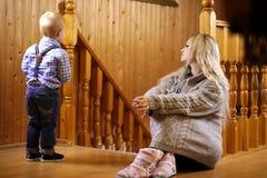 Wychowywa z dziecka obsiadaniem na podłoga blisko drewnianego poręcza Zdjęcia Stock